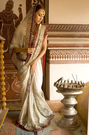 sari: Beautiful young indian woman in traditional clothing with incense bridal makeup and oriental jewelry. Girl bollywood dancer in Sari in the eastern palace. Beautiful princess praying. Eastern fairy tale