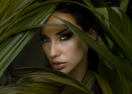 smokey: Sexy beautiful woman hiding behind the palm leaves. Portrait of beautiful stylish young woman with smokey eyes, wildness