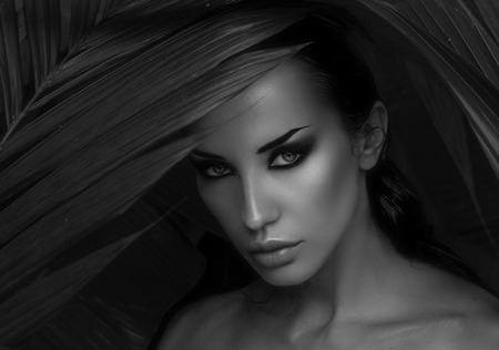 wildness: Sexy beautiful woman hiding behind the palm leaves like a panther in the in the tropical forest in India. Portrait of beautiful caucasian stylish young woman with smokey eyes, wildness Stock Photo