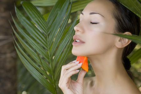 skin care: Beautiful caucasian woman having fresh papaya natural facial mask apply, skin care and wellness. Fresh papaya fruit. Facial mask of papaya slices at spa salon Stock Photo