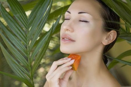 Beautiful caucasian woman having fresh papaya natural facial mask apply, skin care and wellness. Fresh papaya fruit. Facial mask of papaya slices at spa salon.