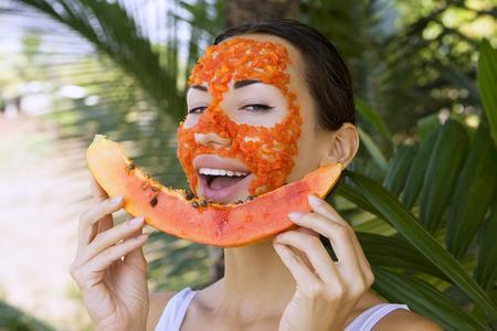 masaje facial: Mujer caucásica hermosa que tiene aplicar papaya fruta fresca máscara facial natural, cuidado de la piel antioxidante y el bienestar. Vitamina máscara facial de rodajas de papaya en el salón de spa (al aire libre). Saludable comida exótica