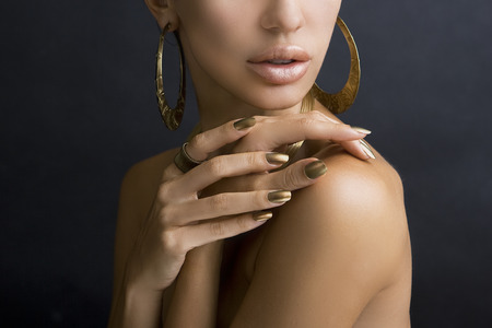 Beautiful Women Lips with Stylish Golden Shiny Lipstick and Hands with Golden Manicure and Gold Jewelery on dark background. Makeup, Fashion, Beauty. Nail Care