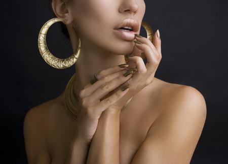 pedicura: Hermosas mujeres labios con estilo de oro brillante del lápiz labial y Manos con oro Manicura y Oro Joyería en fondo oscuro. Maquillaje, Moda, Belleza. Cuidado De Uñas Foto de archivo