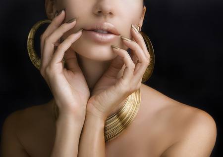 the lipstick: Beautiful Women Lips with Stylish Golden Shiny Lipstick and Hands with Golden Manicure and Gold Jewelery on dark background. Makeup, Fashion, Beauty. Nail Care