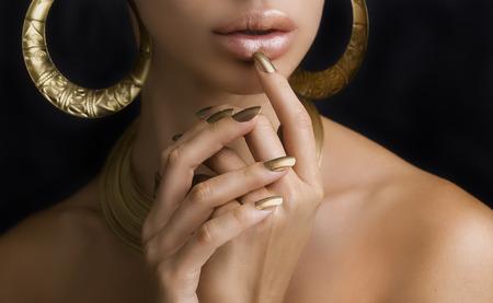 manicura: Hermosas mujeres labios con estilo de oro brillante del lápiz labial y Manos con oro Manicura y Oro Joyería en fondo oscuro. Maquillaje, Moda, Belleza. Cuidado De Uñas Foto de archivo