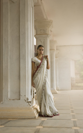Beautiful young Indian Woman in Traditional Clothing with Bridal Makeup and Oriental Jewelry. Girl Bollywood dancer in Sari posing outdoor near the Eastern Palace. Eastern fairy tale Stockfoto