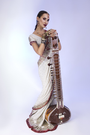 oriental girl: Beautiful Young Indian Woman in Traditional Sari Clothing with oriental jewelry, Bridal Makeup Posing with Sitar. Beautiful Bollywood Girl full height. Eastern fairy tale  (blue lens effect)
