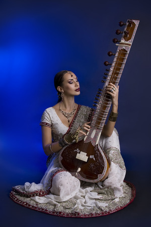 oriental girl: Beautiful Young Indian Woman in Traditional Sari Clothing with oriental jewelry, Bridal Makeup Playing the Sitar. Beautiful Bollywood Girl. Eastern fairy tale  (blue lens effect)