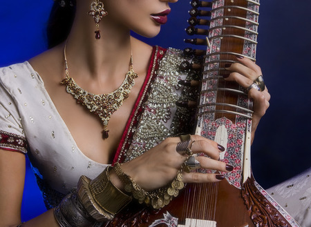 jewelry: Beautiful Young Indian Woman in Traditional Sari Clothing with oriental jewelry, Bridal Makeup Playing the Sitar. Beautiful Bollywood Girl. Eastern fairy tale  (blue lens effect)
