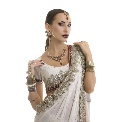 oriental girl: Beautiful Young Indian Woman in white and red Traditional Clothing with Bridal Makeup and Oriental Jewelry. Beautiful Girl Bollywood dancer (Bellydancer) in Sari. Eastern fairy tale Stock Photo