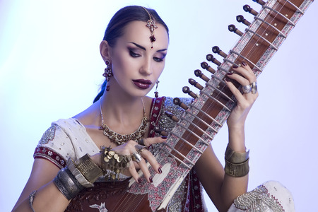 Beautiful Young Indian Woman in Traditional Sari Clothing with oriental jewelry, Bridal Makeup Playing the Sitar. Beautiful Bollywood Girl. Eastern fairy tale  (blue lens effect)
