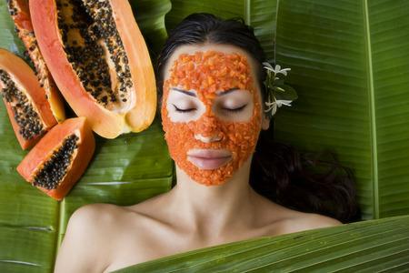 piel: Hermosa mujer caucásica que tiene aplicar papaya fresca máscara facial natural, cuidado de la piel y el bienestar (al aire libre). Vitamina máscara facial de rodajas de papaya en el salón spa