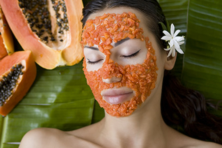 facial spa: Beautiful caucasian woman having fresh papaya natural facial mask apply, skin care and wellness (outdoors). Facial vitamin mask of papaya slices at spa salon