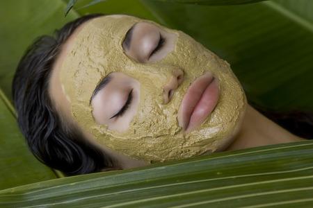 masaje facial: Spa al aire libre, mujer joven hermosa que miente con la arcilla a base de hierbas máscara facial verde natural en su cara, cuidado de la piel y el bienestar Foto de archivo