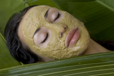 Spa Outdoor, Beautiful young woman lying with natural green herbal clay facial mask on her face, skin care and wellness