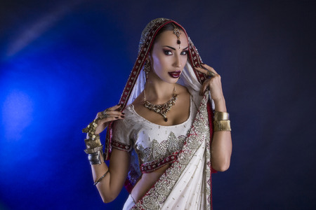 bollywood woman: Beautiful Young Indian Woman in Traditional Clothing with Bridal Makeup and Oriental Jewelry. Beautiful Girl Bollywood dancer (Bellydancer) in Sari. Eastern fairy tale (blue lens effect) Stock Photo