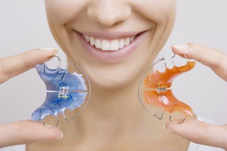 Beautiful Smiling Girl Holding blue Retainer, Braces for Teeth. Orthodontics Dental Theme, Methods of Teeth (Bite) Correction