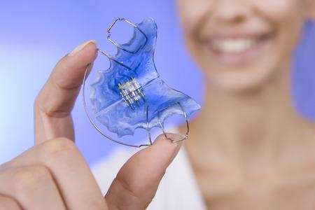 Beautiful Smiling Girl Holding blue Retainer, Braces for Teeth. Orthodontics Dental Theme, Methods of Teeth (Bite) Correction, Close-up