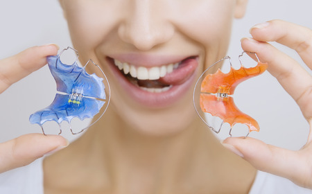beautiful teeth: Beautiful Smiling Girl with Retainer for Teeth sticking her Tongue out. Orthodontics Dental Theme, Methods of Teeth (Bite) Correction, Close-up Stock Photo