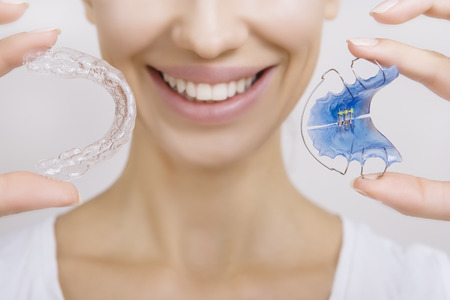 braces: Beautiful Smiling girl Holding Retainer for Teeth (Dental Braces) and Individual Tooth Tray. Orthodontics Dental Theme, Methods of Teeth (Bite) Correction, Close-up Stock Photo