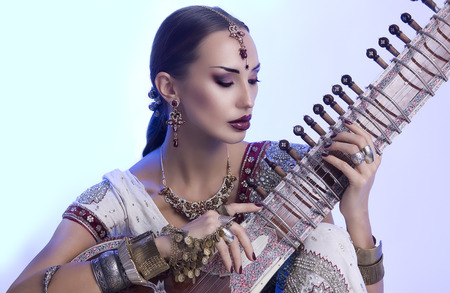stringed: Beautiful Young Indian Woman in Traditional Sari Clothing with oriental jewelry, Bridal Makeup Playing the Sitar. Beautiful Bollywood Girl. Eastern fairy tale  (blue lens effect)