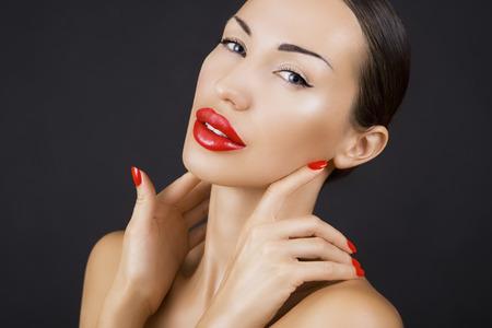 labios sexy: Atractiva joven hermosa niña morena con labios rojos y Esmalte de uñas rojo, brillante relucir brillante del primer del maquillaje en el fondo oscuro (negro) Foto de archivo