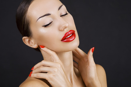 glistening: Sexy Young Beautiful Brunette Girl with Red Lips and Red Nail Polish, Bright Glistening  Shining Make-up Closeup on Dark Background (black) Stock Photo