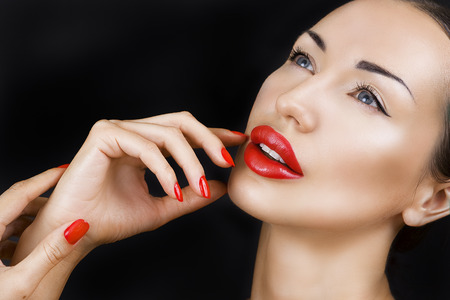 glistening: Sexy Young Beautiful Brunette Girl with Red Lips and Red Nail Polish, Bright Glistening Make-up Closeup on Dark Background, Highlighter
