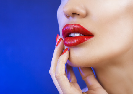 Sexy Young Beautiful Girl with Red Lips and Red Nail Polish, Bright Make-up Closeup on Blue Background
