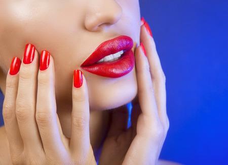 labios rojos: Sexy joven hermosa muchacha con los labios rojos y Esmalte de uñas rojo, brillante relucir brillante Primer del maquillaje en Sexy chica joven hermosa morena con labios rojos y Esmalte de uñas rojo, brillante relucir brillante Primer Maquillaje sobre fondo azul