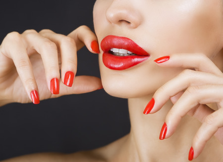 glistening: Sexy Young Beautiful Brunette Girl with Red Lips and Red Nail Polish, Bright Glistening Shining Make-up Closeup on Dark Background