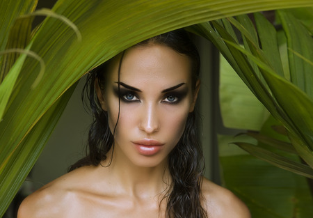 tropical forest: Makeup. Sexy beautiful woman hiding behind the palm leaves like a panther in the tropical forest in India. Portrait of beautiful caucasian stylish young woman with smokey eyes, wildness