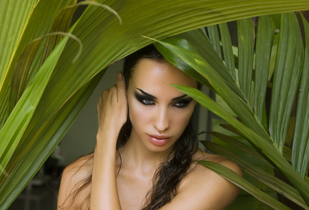 wildness: Makeup. Sexy beautiful woman hiding behind the palm leaves like a panther in the tropical forest in India. Portrait of beautiful caucasian stylish young woman with smokey eyes, wildness.