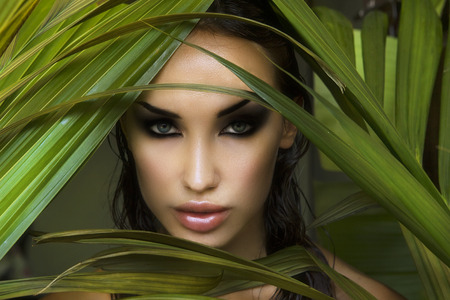 Makeup. Sexy beautiful woman hiding behind the palm leaves like a panther in the tropical forest in India. Portrait of beautiful caucasian stylish young woman with smokey eyes, wildness.