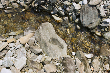 downshifting: Wet Footprints on stone, mountain river landscape, trek to Pokhara, Nepal