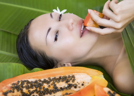 exotic food: Beautiful caucasian woman with fresh fruit papaya (outdoors). Healthy Natural Exotic Food, Luxury Rest in the Tropical countries of Asia