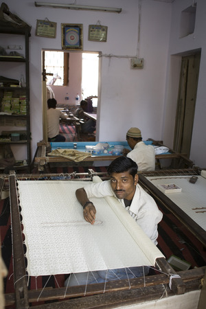 handloom: VARANASI, INDIA – DEC 9, 2013: Unidentified Indian man embroidering a traditional sari cloth, on old fabric factory on Dec 9, 2013, Varanasi, India. Textile industry in Varanasi preserved ancient traditions
