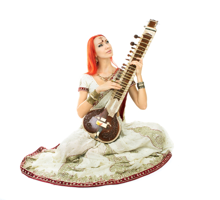 sexy redhead: Beautiful Young Redhead Sexy Woman in Traditional Indian Sari Clothing with Oriental Jewelry and Bridal Makeup Playing Raga the Sitar. Beautiful hot Bollywood Girl. Eastern Music