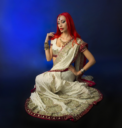 sexy dancer: Beautiful Redhead Young Sexy Woman in Traditional Indian Clothing with Bridal Makeup and Oriental Jewelry. Beautiful Girl Bollywood dancer (Bellydancer) in Sari. Eastern fairy tale (blue lens effect) Stock Photo
