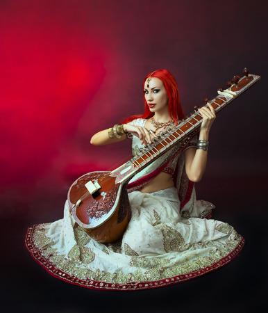 instrumentos musicales: Redhead hermoso joven mujer atractiva en el tradicional india Sari Ropa con joyer�a oriental y maquillaje nupcial Jugar Raga el Sitar. Chica de Bollywood caliente Hermosa. M�sica del Este Foto de archivo