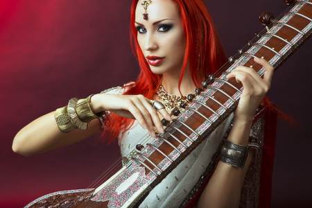asian girl face: Beautiful Young Redhead Sexy Woman in Traditional Indian Sari Clothing with Oriental Jewelry and Bridal Makeup Playing Raga the Sitar. Beautiful hot Bollywood Girl. Eastern Music