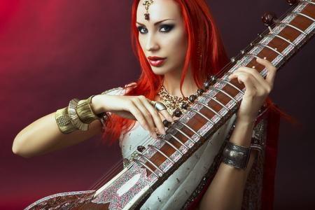chica sexy: Redhead hermoso joven mujer atractiva en el tradicional india Sari Ropa con joyería oriental y maquillaje nupcial Jugar Raga el Sitar. Chica de Bollywood caliente Hermosa. Música del Este Foto de archivo