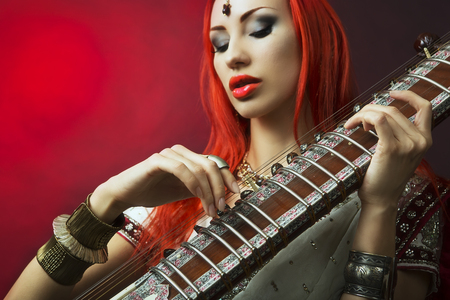 oriental girl: Beautiful Young Redhead Sexy Woman in Traditional Indian Sari Clothing with Oriental Jewelry and Bridal Makeup Playing Raga the Sitar. Beautiful hot Bollywood Girl. Eastern Music
