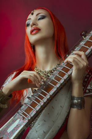 Beautiful Young Redhead Sexy Woman in Traditional Indian Sari Clothing with Oriental Jewelry and Bridal Makeup Playing Raga the Sitar. Beautiful hot Bollywood Girl. Eastern Music