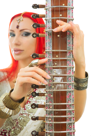 bollywood: Beautiful Young Redhead Sexy Woman in Traditional Indian Sari Clothing with Oriental Jewelry and Bridal Makeup Playing Raga the Sitar. Beautiful hot Bollywood Girl. Eastern Music