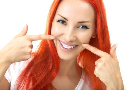 Schöne lächelnde Redhead Girl zeigt Halter, Klammern für Zähne. Kieferorthopädie Zahnärztliche Themen, Methoden der Zähne (Biss) Korrektur, Close-up Standard-Bild