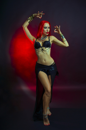 Bellydance, Tribal Fusion. Beautiful Redhead Young Woman in Sexy Clothing with Eastern Makeup and Luxury Oriental Jewelry. Beautiful Girl Hot Bollywood Dancer (Sensitive Bellydancer). Eastern fairy tale, Harem. Stock Photo