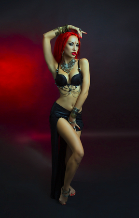 bellydance: Bellydance, Tribal Fusion. Beautiful Redhead Young Woman in Sexy Clothing with Eastern Makeup and Luxury Oriental Jewelry. Beautiful Girl Hot Bollywood Dancer (Sensitive Bellydancer). Eastern fairy tale, Harem Stock Photo