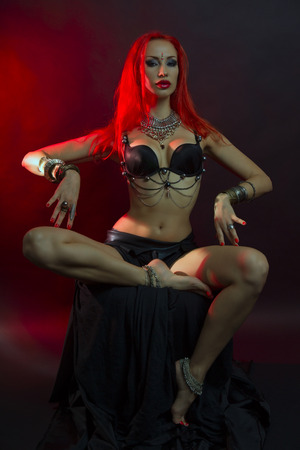 tribal dance: Bellydance, Tribal Fusion. Beautiful Redhead Young Woman in Sexy Clothing with Eastern Makeup and Luxury Oriental Jewelry. Beautiful Girl Hot Bollywood Dancer (Sensitive Bellydancer). Eastern fairy tale, Harem Stock Photo
